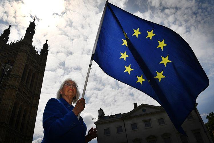 Seorang pendukung Uni Eropa mengibarkan bendera Uni Eropa di depan gedung parlemen di London, 13 Juni 2018.