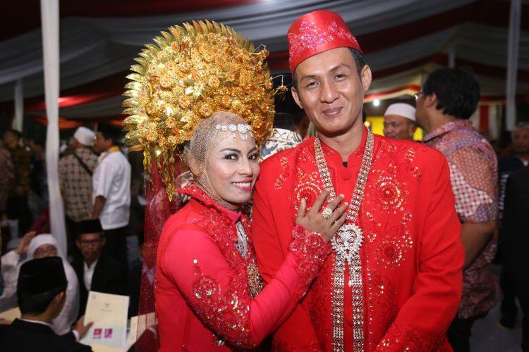 Sepasang pengantin berpose usai mengikuti nikah massal di jalan MH Thamrin, Jakarta Pusat, Minggu (31/12/2017). Nikah massal yang diadakan oleh pemerintah DKI Jakarta ini diikuti sebanyak 437 pasangan pengantin dari berbagai usia.