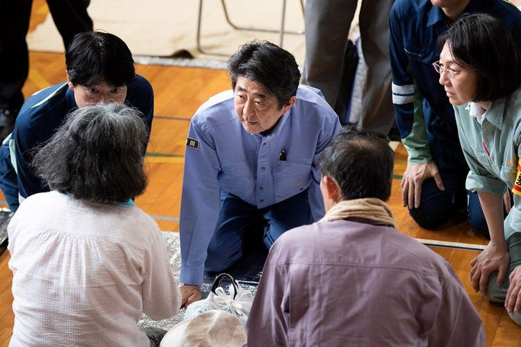 Perdana Menteri Jepang Shinzo Abe saat berbicara dengan beberapa korban terdampak bencana longsor di pusat evakuasi warga di kota Kurashiki, prefektur Okayama, Rabu (11/7/2018).