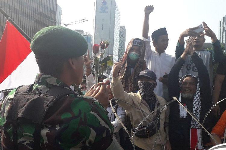 Seorang prajurit TNI menerima bunga mawar dari massa peserta aksi unjuk rasa di depan Kantor Bawaslu RI di Jalan MH Thamrin, Jakarta Pusat, Rabu (22/5/2019).