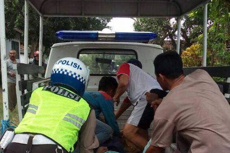Anggota Satlantas Polres Magetan dan warga mengevakuasi Paiman korban kecelakaan tabrakan sepeda motor konvoi kelulusan SMA di Jalan Umum Jurusan Bangsri-Sumberagung ,  di Desa Bangsri, Kecamatan Ngariboyo, Kabupaten Magetan, Rabu ( 3/5/2017) siang.