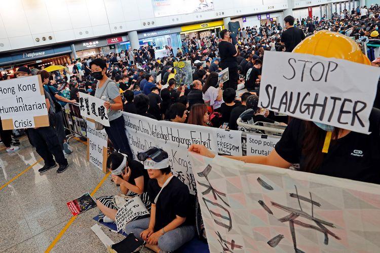Massa pengunjuk rasa pro-demokrasi ketika melakukan aksinya setelah seorang perempuan tertembak di mata dalam aksi protes di Bandara Internasional Hong Kong, Senin (12/8/2019).