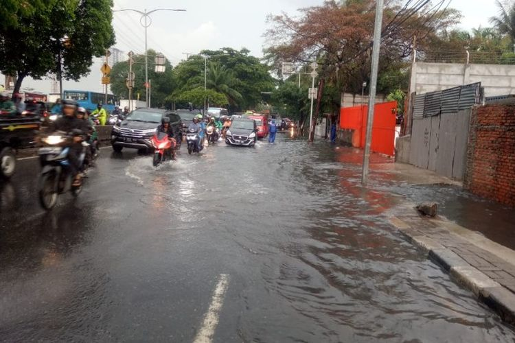 Jalan Daan Mogot Jakarta Barat dari arah menuju Grogol tergenang akibat saluran air yang tak kuat menampung air akibat hujan pada Rabu (12/12/2018).