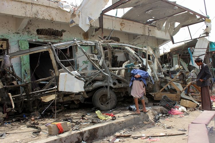 Warga melihat kondisi bus yang hancur akibat serangan yang dilancarkan pasukan koalisi pimpinan Arab Saudi di Yaman.