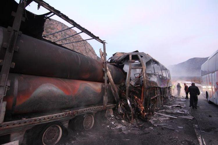 Petugas memeriksa sisa kendaraan bus yang terbakar setelah menabrak truk yang sedang parkir di jalan raya Istanbul-Samsun, kota Osmancik, Turki, Selasa (13/3/2018).
