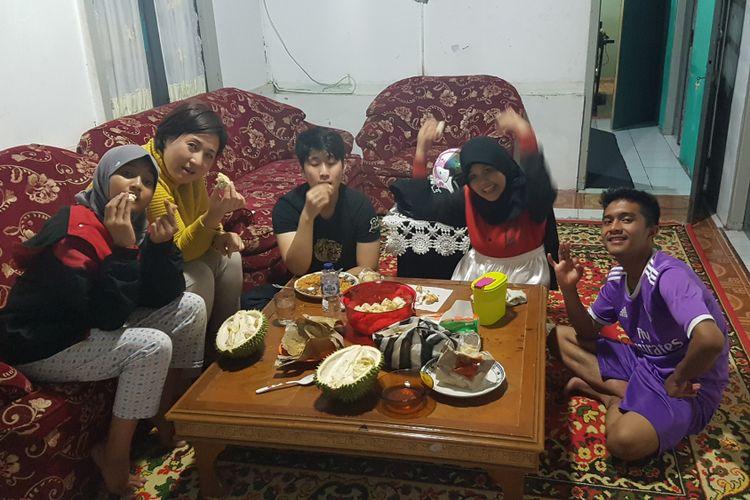 Eje Kim (kedua kiri), profesor asal Korea Selatan yang sangat menyukai durian Indonesia, sedang menyantap bersama anaknya (tengah) dan rekannya di Padang, Sumatera Barat.