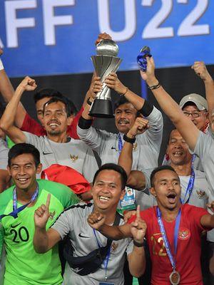 Pelatih Timnas U-22 Indra Sjafri (tengah belakang) mengangkat Piala AFF U-22 seusai penganugerahan piala di Stadion Nasional Olimpiade Phnom Penh, Kamboja, Selasa (26/2/2019). Indonesia menjadi juara setelah mengalahkan Thailand di babak final dengan skor 2-1.
