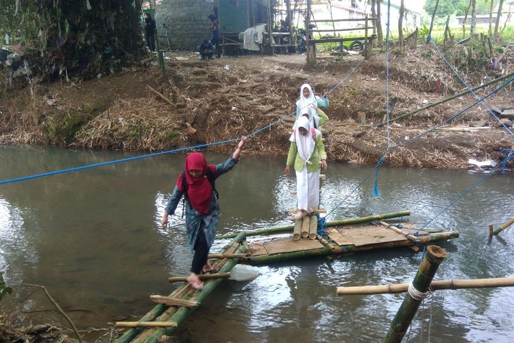 SiswiMadrasah Aliyah (MA) Ummatan Washatan Kecamatan Imogiri, Kabupaten Bantul, Yogyakarta, tertatih melewati jembatan darurat yang terbuat dari bambu melintang di atas sungai celeng. Kamis (4/4/2019)