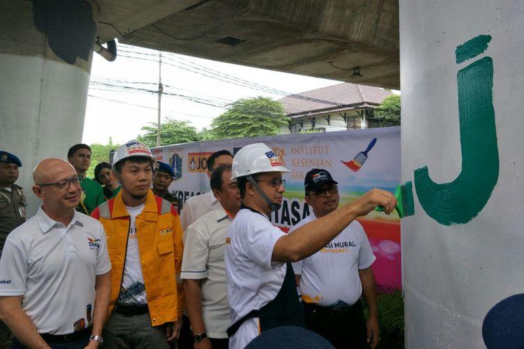 Gubernur DKI Jakarta Anies Baswedan melukis mural di tiang Jalan Layang Non-tol Antasari, Sabtu (10/3/2018).