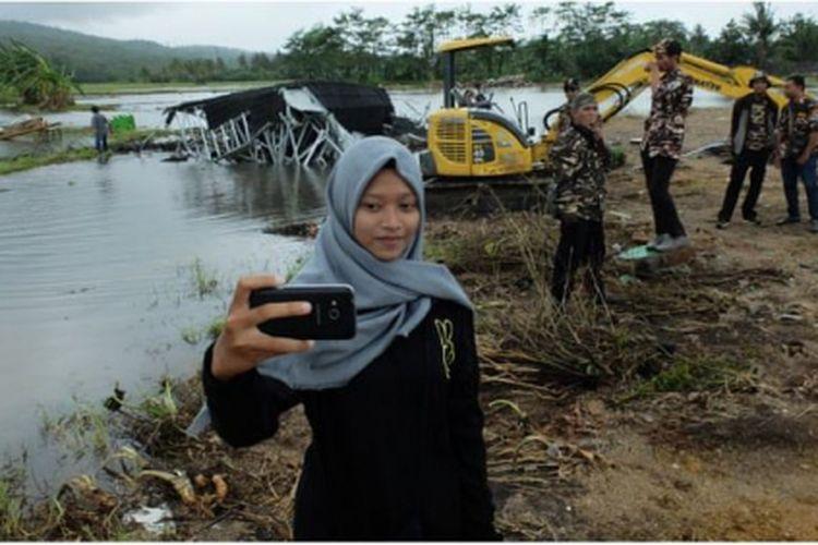 Seorang perempuan muda mengambil swafoto di lokasi bencana tsunami, di Banten.