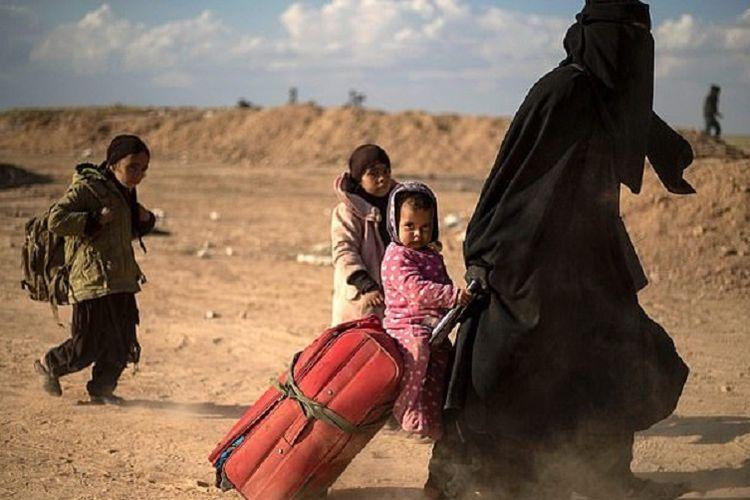 Seorang ibu berjalan sambil membawa tas koper dengan bayinya di atas, dan diikuti dua anaknya ketika meninggalkan Baghouz, kota di Suriah yang menjadi benteng terakhir ISIS.