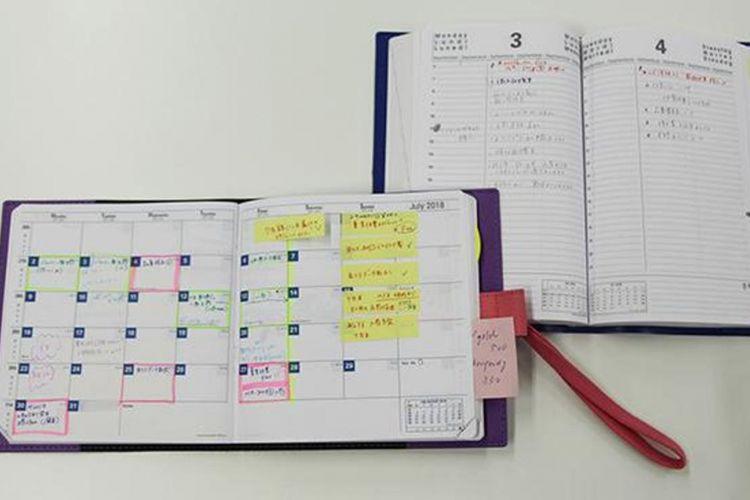Seorang pegawai perempuan penanggung jawab logistik menggunakan dua buku agenda monthly/bulanan dan daily/harian, dan mengisinya jadwal maupun To-Do list.