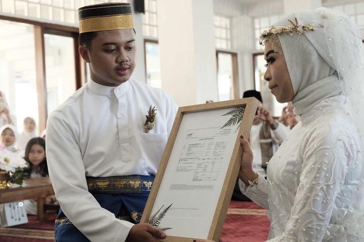 Dwian Wahyu Prabawa (26) dan Sherly Wijayanti Kumayas (25) menunjukkan mahar saham dalam pernikahannya di Boyolali, Jawa Tengah, Minggu (7/7/2019).