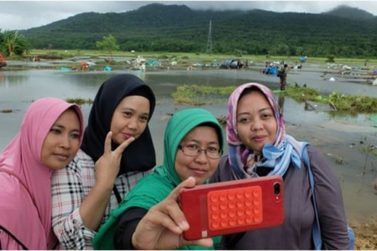 4 orang terlihat mengambil foto diri di dekat lokasi bencana tsunami yang menunjukkan kerusakan parah di belakangnya.