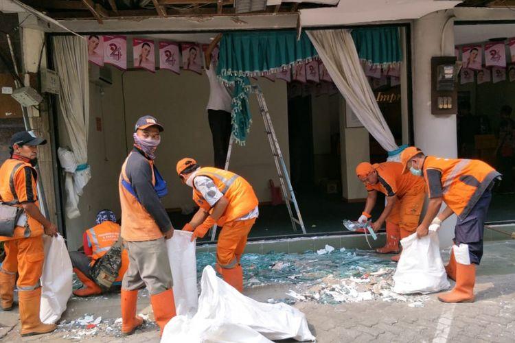 Petugas penanganan prasarana dan sarana umum (PPSU) atau pasukan oranye dan petugas Dinas Lingkungan Hidup membersihkan pecahan-pecahan kaca di lokasi ledakan Ruko Grand Wijaya Center, Jalan Wijaya II, Kebayoran Baru, Jakarta Selatan, Kamis (12/7/2018).