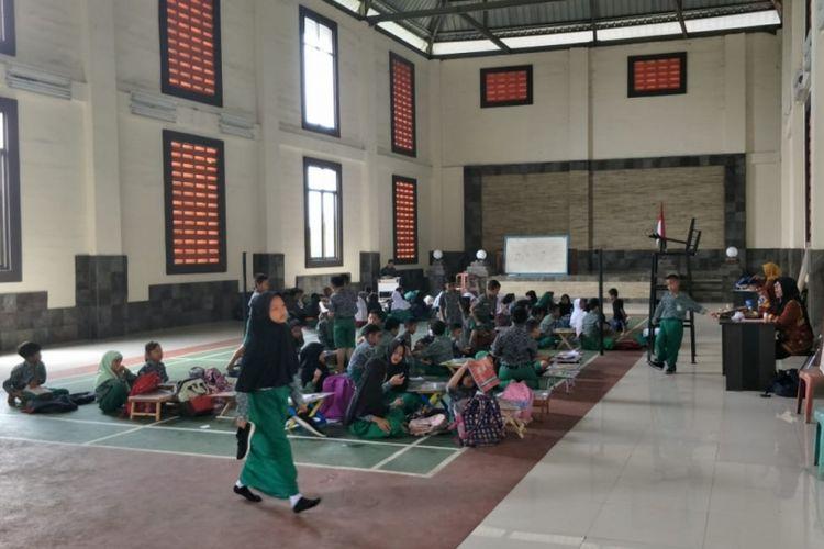 Tampak ratusan siswa SDN 01 Cicau, Kecamatan Cikarang Pusat, Kabupaten Bekasi belajar di GOR Kantor Desa Cicau karena atap dua ruang kelas roboh, Kamis (7/2/2019).