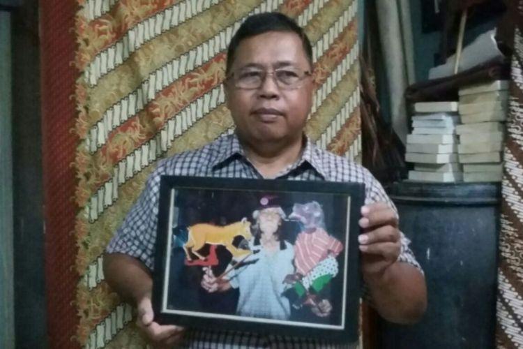 Supriantoro saat menunjukan foto Alm Ledjar Subroto ketika membawa wayang kancil