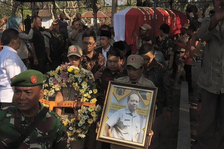 Peti jenazah Sutopo dipanggul para petugas BPBD sebelum dimasukkan ke liang lahat di TPU Sasonolayu, Siswodipuran, Boyolali, Jawa Tengah, Senin (8/7/2019).