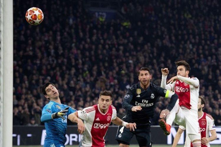 Nicolas Tagliafico lebih cepat daripada Thibaut Courtois dan Sergio Ramos yang coba memotong bola pada pertandingan Ajax Amsterdam vs Real Madrid di Johan Cruyff Arena dalam babak 16 besar Liga Champions.