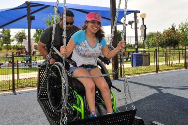 Seorang pengunjung mencoba ayunan kursi roda.