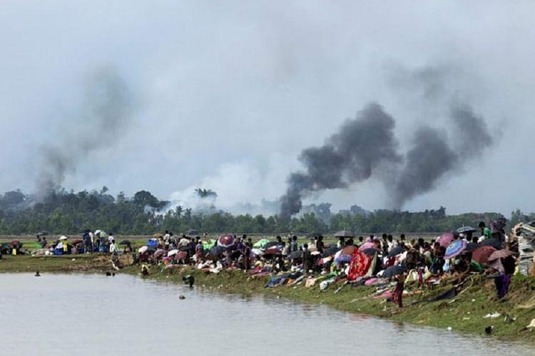 Asap hitam mengepul di banyak tempat di sebuah desa di negara bagian Rakhine, Myanmar, yang diyakini ada pembakaran rumah-rumah warga Rohingya. Warga korban pun hanya memandang sedih