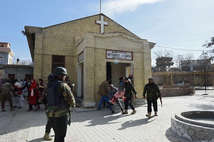 Petugas keamanan Pakistan terlihat sedang menyelamatkan seorang wanita yang terluka setelah pelaku bom bunuh diri menyerang gereja Metodis pada Minggu (17/12/2017), di Quetta, Pakistan. (AFP/Banaras Khan)