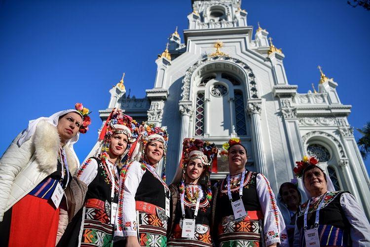 Perempuan mengenakan kostum tradisional Bulgaria berpose di depan Gereja St Stephen Bulgaria, yang juga dikenal sebagai Gereja Besi, setelah peresmian pembukaan kembali, di Istanbul, Minggu (7/1/2018). (AFP/Ozan Kose)