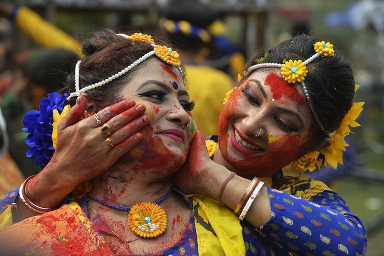 Penduduk di India mengolesi temannya dengan bubuk berwarna selama perayaan festival Holi di Siliguri, Kamis (1/3/2018). (AFP/Diptendu Dutta).