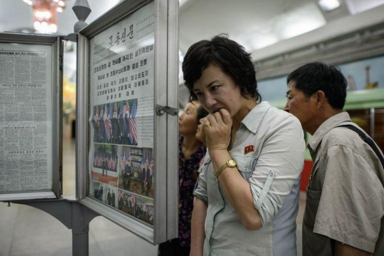 Penumpang kereta yang berada di stasiun Pyongyang, Korea Utara, membaca harian Rodong Sinmun yang memberitakan pertemuan pemimpin Korut Kim Jong Un dan Presiden AS Donald Trump.  (AFP/Ed Jones)