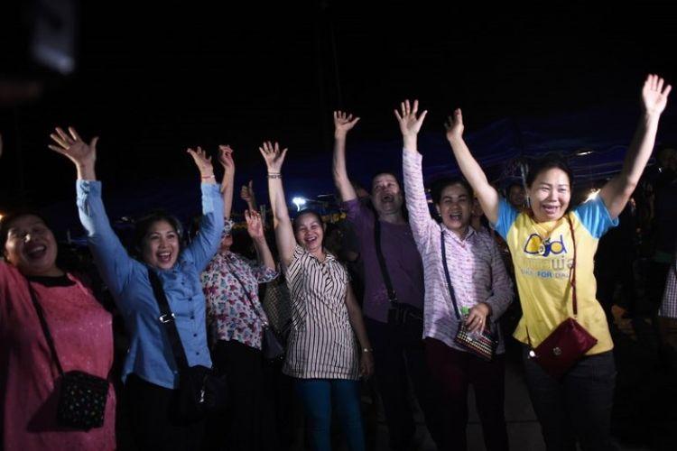 Relawan pada Selasa (10/7/2018) merayakan keberhasilan misi penyelamatan tim sepak bola remaja dan pelatih mereka yang terjebak di goa Tham Luang, Thailand. (AFP/Ye Aung Thu)