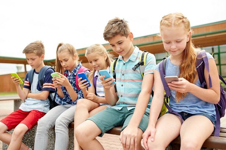 Ilustrasi anak-anak sekolah pakai ponsel.