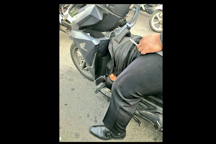 Ilustrasi seorang pengendara motor yang sedang merokok. Perilaku ini sebenarnya dilarang karena dapat membahayakan pengendara lainnya.