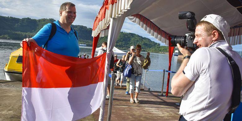 Wisatawan kapal pesiar Aida Vita Cruise berpose dengan Bendera Merah Putih saat tiba di Pelabuhan Lembar, Lombok Barat, NTB, Minggu (3/2/2019). Sebanyak 1170 wisatawan asing asal Jerman melakukan kunjungan wisata ke sejumlah lokasi di Lombok seperti Gili Trawangan, Mandalika, Taman Mayura dan Sekotong sebelum melanjutkan perjalanan ke Pulau Komodo.