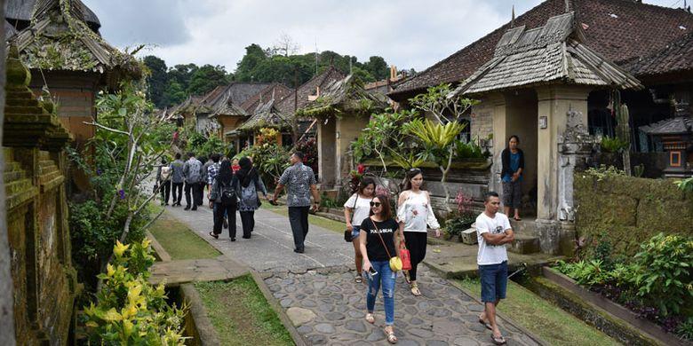 Sejumlah wisatawan mengunjungi Desa Adat Penglipuran di Kubu, Kabupaten Bangli, Bali, Kamis (19/7/2018). Desa yang telah berdiri sejak 700 tahun silam pada masa Kerajaan Bangli tersebut mendapat predikat dari TripAdvisor sebagai desa terbersih sedunia pada 2016 dan saat ini menjadi destinasi favorit wisatawan untuk menikmati suasana perkampungan tradisional adat khas Bali.
