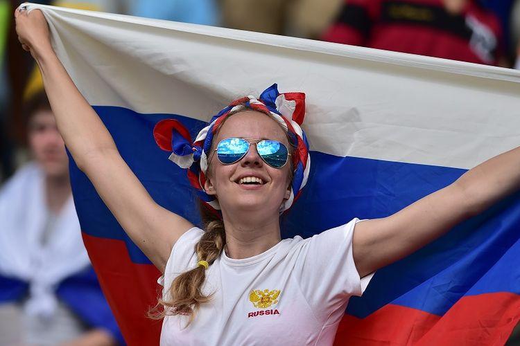 Seorang fans perempuan mengibarkan bendera Rusia sebagai dukungan terhadap tim nasional mereka yang berlaga pada Piala Dunia 2014 di Brasil.