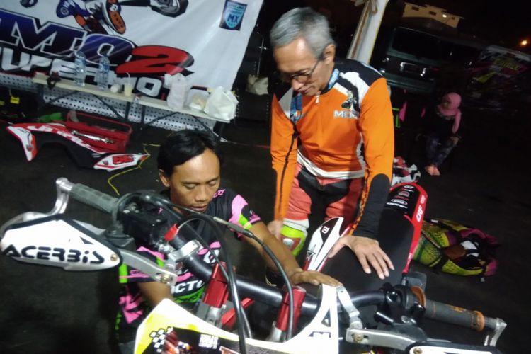 Harmono Mono bersama mekaniknya sedang mencari settingan yang pas untuk motornya jelang kualifikasi kejuaraan supermoto Trial Game Asphat (TGA) kelas FFA 450 Non Pro berlangsung pada Sabtu(4/6/2018).