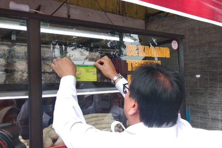 Sekda Provinsi SUmsel Nasrun Umar memasang stiker bebas formalin usai meninjau bersama BPOM Palembang di sentral kampung pempek di jalan Mujahidin , Palembang, Sumatera Selatan, Senin (25/6/2018).
