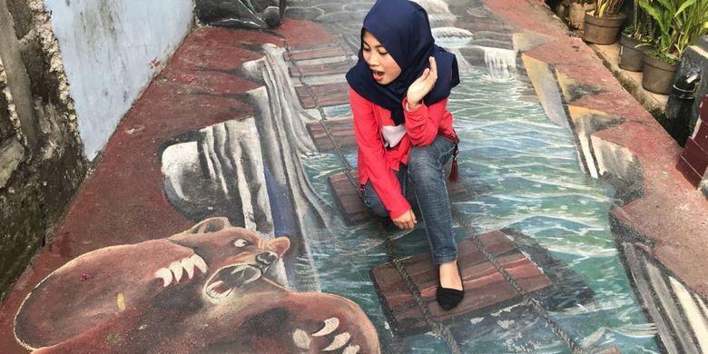 Seorang pengunjung berfoto di lukisan 3D Jalan Krakatau VII, Sukmajaya, Depok pada Senin (11/6/18).
