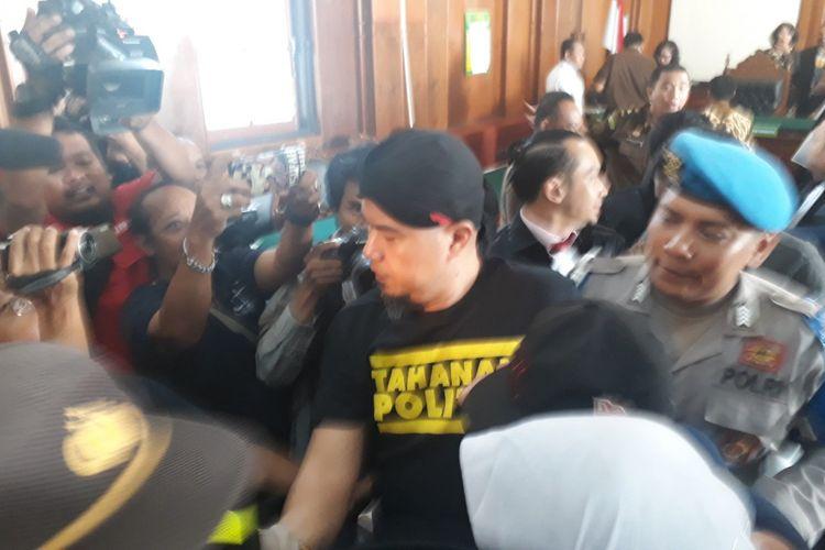 Ahmad Dhani digiring ke mobil tahanan kejaksaan usai sidang di Pengadilan Negeri Surabaya, Kamis (7/2/2019).
