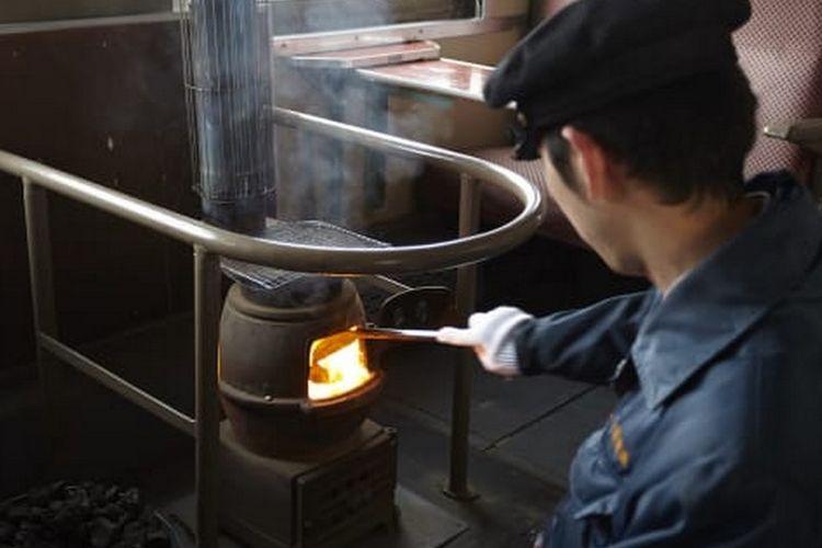 Petugas membakar bara di kompor untuk menghangatkan suhu kabin kereta api.