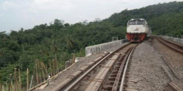 Kereta api Jakarta-Bandung saat melintasi jalur rel kereta api yang ambles dan bahu jalannya bergeser satu meter, di Kampung Cisuren, Desa Mekargalih, Kecamatan Jatiluhur, Kabupaten Purwakarta, Minggu (12/3/2017).