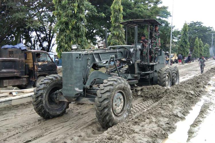 Alat berat yang digunakan untuk membersihkan material banjir bandang yang menutupi ruas Jalan Kemiri, Sentani, Senin (18/3/2019)