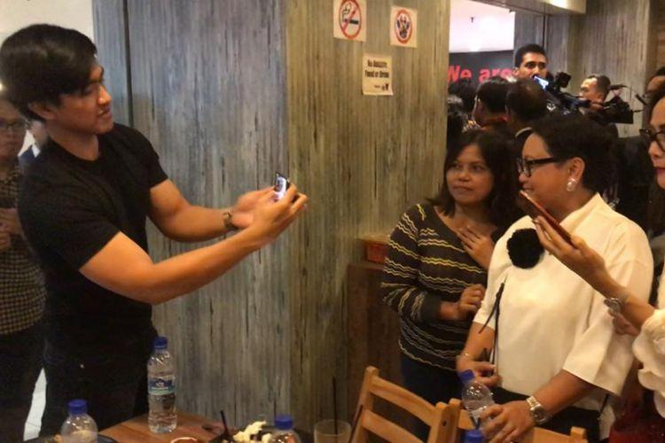 Momen saat Kaesang Pangarep mengambil foto WNI yang sedang berpose bersama Menteri Luar Negeri Retno Marsudi, Selasa (13/11/2018).