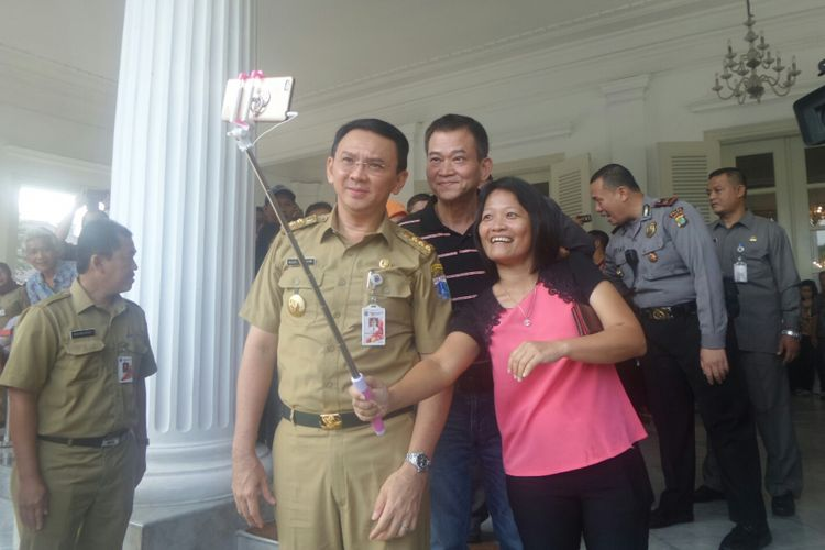 Gubernur DKI Jakarta Basuki Tjahaja Purnama melayani permintaan foto warga pada hari pertamanya aktif di Balai Kota, Senin (17/4/2017).