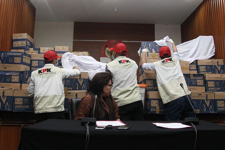 Penyidik didampingi Wakil Ketua KPK Basaria Panjaitan, menunjukkan barang bukti hasil operasi tangkap tangan (OTT) yang menjerat anggota Fraksi Golkar DPR, Bowo Sidik Pangarso, saat memberikan keterangan pers, di Gedung KPK Merah Putih, Jakarta, Kamis (28/3/2019). Uang senilai Rp 8 miliar yang dibagi dalam 84 kardus atau 400 ribu amplop dengan pecahan Rp 20.000 dan Rp 50.000 tersebut diduga sebagai suap untuk pelaksanaan kerja sama Pengangkutan Bidang Pelayaran antara PT Pupuk Indonesia Logistik (PILOG) dan PT Humpuss Transportasi Kimia (HTK), dan diduga digunakan untuk membantu biaya kampanye Pemilu 2019.