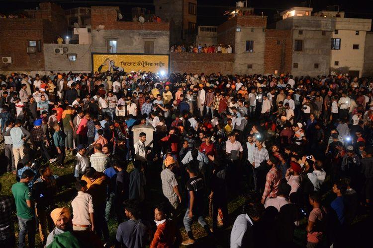 Warga berkumpul di sekitar lokasi insiden kereta api yang menabrak kerumunan pengunjung festival Dussehra di Kota Amritsar, India, pada Jumat (19/10/2018).