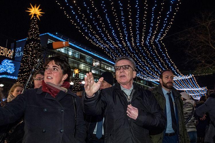 Menteri Dalam Negeri Jerman Thomas de Maiziere (tengah) meninjau pasar Natal di Berlin.