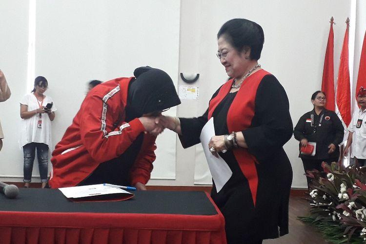 Ketua DPP PDI-P Tri Rismaharini mencium tangan Ketua Umum PDI-P Megawati Soekarnoputri di Kantor DPP PDI-P, Senin (19/8/2019).(KOMPAS.com/Ardito Ramadhan D)