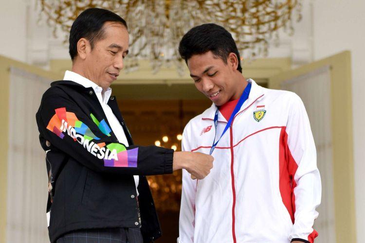 Presiden Joko Widodo (kiri) menerima peraih medali emas lari 100 meter kejuaraan dunia Atletik U20 di Tampere, Finlandia, Lalu Muhammad Zohri, di Istana Bogor, Jawa Barat, Rabu (18/7/2018). Presiden berpesan kepada Zohri untuk tetap berlatih guna meningkatkan prestasi yang diraih dan selalu rendah hati.