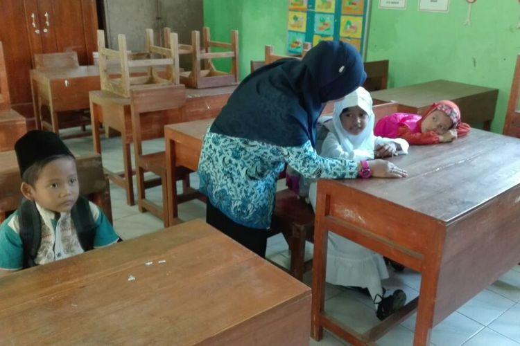Guru SDN Sukosari, Kelurahan Sukosari, Kecamatan Kartoharjo, Kota Madiun berbincang dengan salah satu siswa baru kelas satu. Meski berada di tengah kota, SDN Sukosari hanya mendapatkan tiga siswa baru.